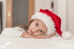 Niña con el sombrero para Papá Noel que espera de la Navidad en casa en Foto de archivo libre de regalías