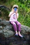 Niña con el teléfono móvil en rocas Imagen de archivo libre de regalías