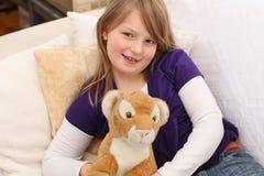 Niña con el tigre del juguete en el sofá Fotos de archivo