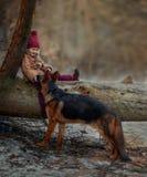 Niña con el 6to perrito de los meses del pastor alemán en la primavera temprana imagen de archivo