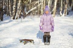 Niña con el trineo en el invierno Imagenes de archivo