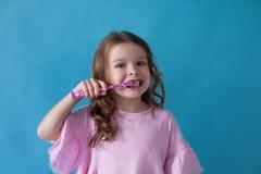 Niña con hacia fuera un diente con una abolladura del cepillo de dientes foto de archivo libre de regalías