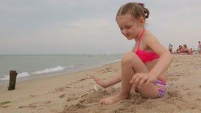 Niña con la arena en la playa metrajes