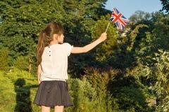 Niña con la bandera de Gran Bretaña en su mano, en parque soleado del verano foto de archivo