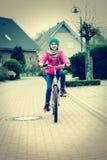 Niña con la bicicleta en el camino. Imagen retra Fotografía de archivo