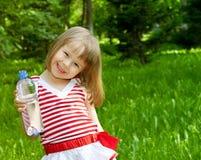 Niña con la botella plástica de agua mineral Imagen de archivo