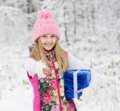 Niña con la caja de regalo azul que muestra los pulgares para arriba en bosque del invierno Fotos de archivo