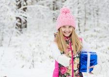 Niña con la caja de regalo que muestra los pulgares para arriba en bosque del invierno Foto de archivo