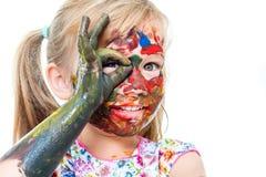 Niña con la cara pintada que mira furtivamente a través del agujero de finger Foto de archivo libre de regalías