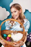 Niña con la cesta con los huevos del color y el conejito de pascua blanco Imagen de archivo libre de regalías