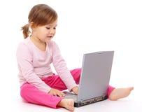 Niña con la computadora portátil Foto de archivo libre de regalías