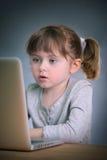 Niña con la computadora portátil Foto de archivo
