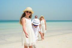 Niña con la familia que camina a lo largo de una playa Imagenes de archivo