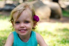 Niña con la flor púrpura en su cabeza en hierba verde Imagen de archivo libre de regalías