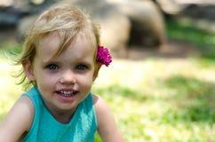Niña con la flor púrpura en su cabeza en hierba verde Imagen de archivo