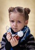 Niña con la medicina de la tos que tiene una mirada preocupante Fotos de archivo