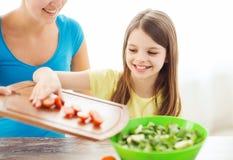 Niña con la madre que añade los tomates a la ensalada Fotografía de archivo