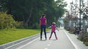 Niña con la madre que monta en Rollerblades metrajes