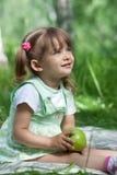 Niña con la manzana verde en sus manos Imagen de archivo libre de regalías