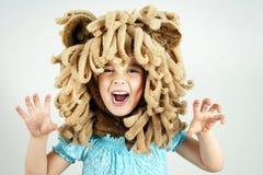 Niña con la melena del león Imagenes de archivo