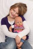 Niña con la muñeca en el sofá Fotos de archivo