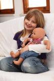 Niña con la muñeca en el sofá Imagenes de archivo