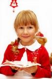Niña con la oblea de la Nochebuena en la placa imagen de archivo