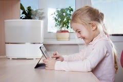 Niña con la PC de la tableta que se sienta cerca del humectador y de la sonrisa Foto de archivo