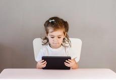 Niña con la PC de la tableta que se sienta en la tabla Fotografía de archivo libre de regalías