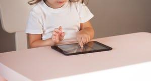Niña con la PC de la tableta que se sienta en la tabla Imagenes de archivo