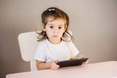 Niña con la PC de la tableta que se sienta en la tabla Foto de archivo libre de regalías