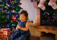 Niña con la piruleta y árbol de navidad y decoración Foto de archivo