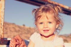 Niña con la sonrisa rizada del pelo rubio Foto de archivo libre de regalías