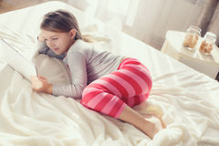Niña con la tableta en cama Foto de archivo libre de regalías