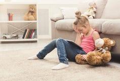 Niña con la tableta que se sienta en piso en casa Fotografía de archivo