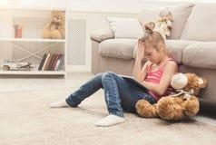 Niña con la tableta que se sienta en piso en casa Foto de archivo