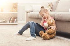 Niña con la tableta que se sienta en piso en casa Fotos de archivo libres de regalías