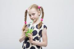 Niña con las coletas que presentan en la polca Dot Dress con la taza de jugo verde Imagen de archivo