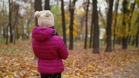 Niña con las hojas de arce que camina en parque del otoño almacen de video