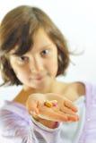 Niña con las píldoras a disposición Foto de archivo libre de regalías