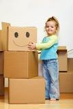Niña con las porciones de cajas de cartón que hace muecas Imagen de archivo libre de regalías