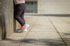 Niña con las zapatillas de deporte y el entrenamiento de las polainas Fotos de archivo