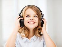 Niña con los auriculares en casa Foto de archivo libre de regalías