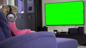 Niña con los auriculares grandes que se sientan en cama y la televisión de observación metrajes