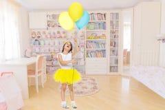 Niña con los globos en sus manos Imagenes de archivo