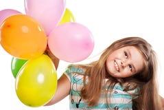 Niña con los globos en un fondo blanco Imagen de archivo libre de regalías