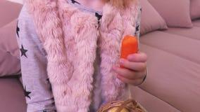 Niña con los huevos de Pascua en cesta y zanahoria en el sofá