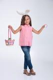 Niña con los oídos del conejito que sostienen la cesta de huevos Imagen de archivo