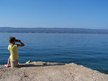 Niña con los prismáticos que mira el mar Fotos de archivo