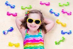 Niña con los vidrios de sol en una playa Foto de archivo libre de regalías